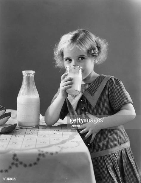 A young girl smiles and puts her hand on her stomach as drinks a glass of milk while leaning against a table