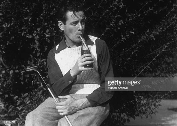 A young man sips a bottle of CocaCola through a straw while sitting with a golf club outdoors