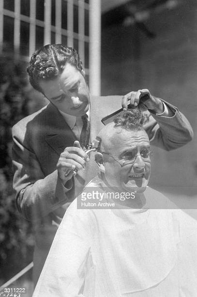 Actor John Gilbert singing whilst cutting the hair of director Marshall Neilan