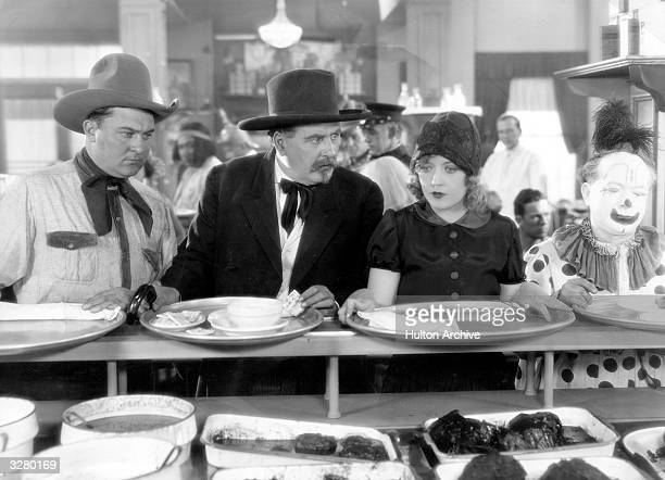 Actors Marion Davies and Dell Henderson in their Wild West costumes blend right in with the eclectic mix of fellow diners at the MGM staff commissary...