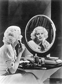 Actress Jean Harlow sitting at her dressing table