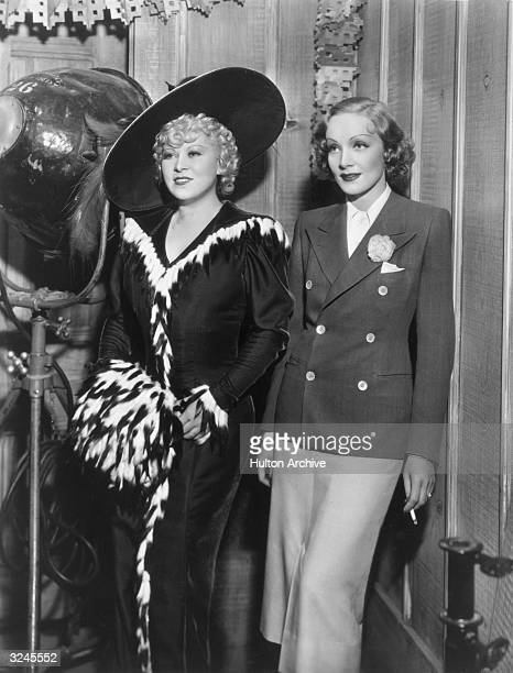 American actor Mae West and German actor Marlene Dietrich standing next to a large studio lamp West is wearing a furtrimmed dress with a matching fur...