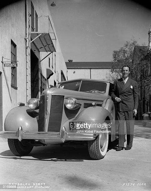 American actor Randolph Scott poses next to his car