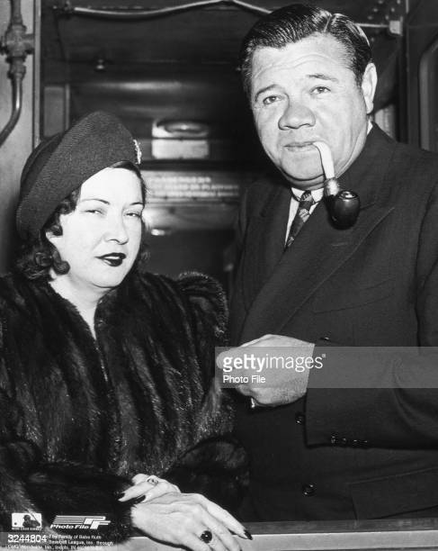 American baseball player George Herman 'Babe' Ruth smokes a pipe while wearing an overcoat and standing beside his wife Claire Merritt Hodgson who is...