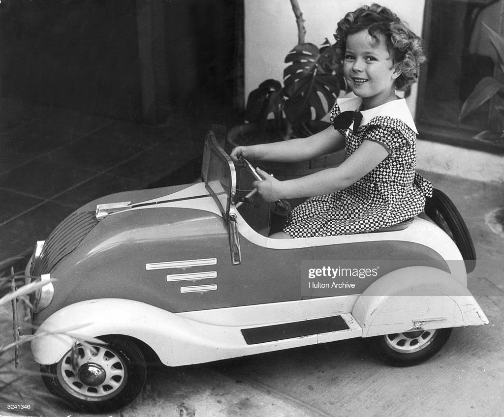 American child actor <a gi-track='captionPersonalityLinkClicked' href=/galleries/search?phrase=Shirley+Temple&family=editorial&specificpeople=69996 ng-click='$event.stopPropagation()'>Shirley Temple</a> smiles while sitting in a toy car.