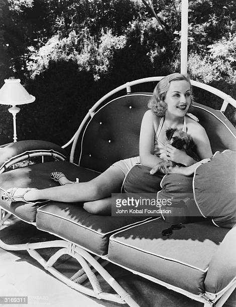American comic actress Carole Lombard lounging on a bamboo couch with a pet dog