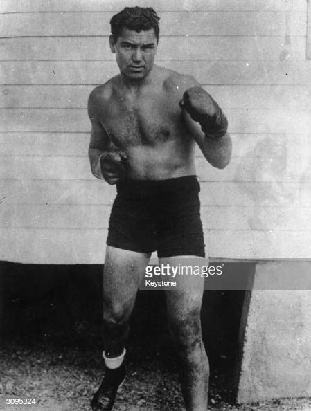American heavyweight boxer Jack Dempsey strikes a sparring pose for the camera while wearing his boxing gloves