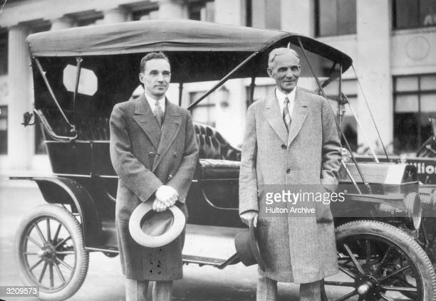 American inventor and industrialist Henry Ford and his son auto executive Edsel Ford posing in front of a Ford automobile