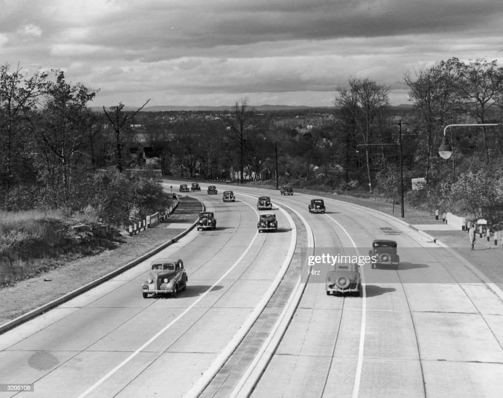 Automobiles travel in both directions along Route 4 near Englewood New Jersey The highway is bordered by trees street lamps and a pedestrian walkway
