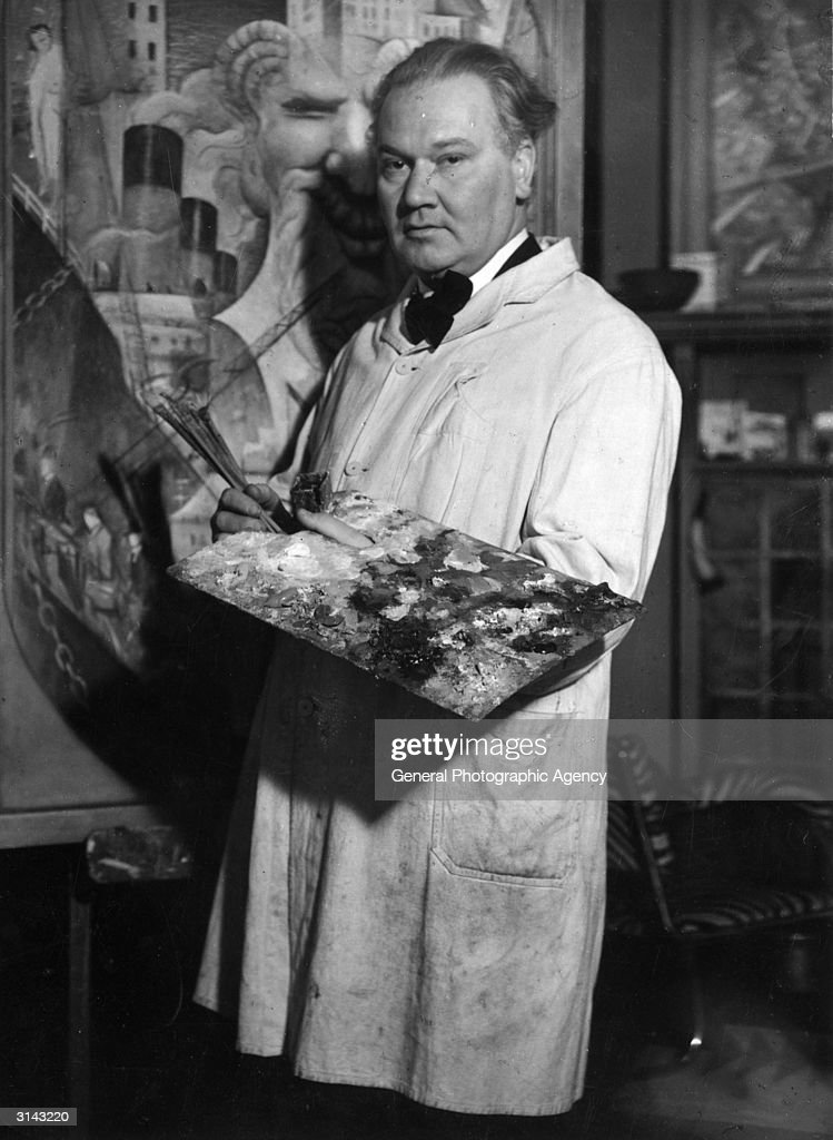 British artist Christopher Richard Wynne Nevinson (1889 - 1946) with an artist's palette and smock in front of one of his paintings.
