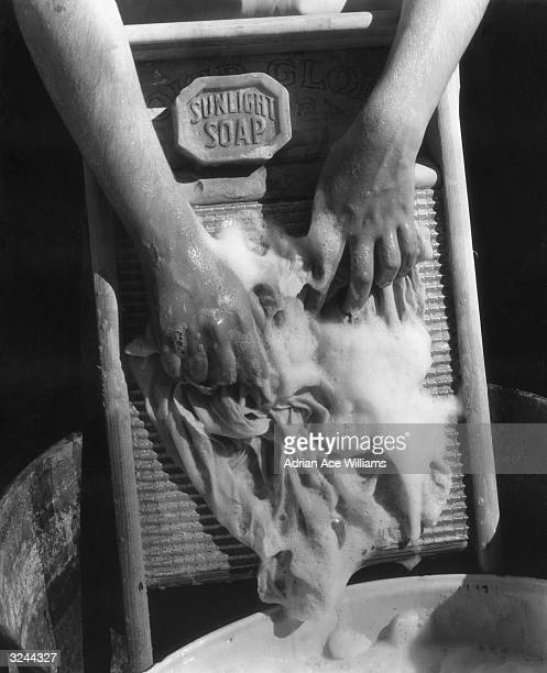 Closeup of a pair of hands scrubbing a sudsy cloth with 'Sunlight Soap' on a washboard over a soapy tub