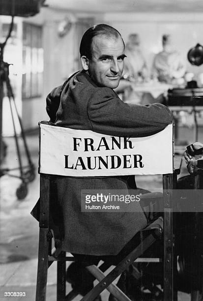 Comic scriptwriter and producer Frank Launder sitting in his chair on set