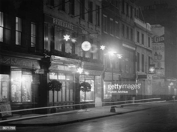 Dean St Soho at night showing the outside of the Quo Vadis restaurant