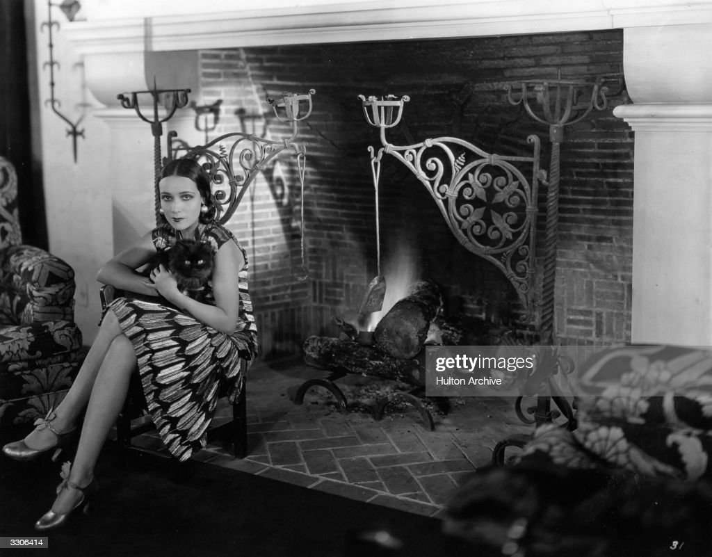 Dolores Del Rio (1905 - 1983) Hollywood film star and wife of MGM's Art Director Cedric Gibbons. Sitting by the fire with her cat 'Joan'.