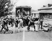 Fulllength group depicting striking workers dumping milk from the back of a delivery truck in the middle of a road as two men try to resist their...