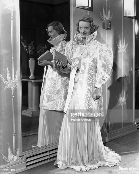 Fulllength image of American actor Bette Davis wearing a silk brocade standing beside a mirror wearing a collared blouse and gown and holding a purse