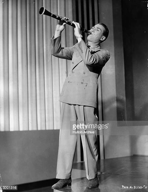 Fulllength image of American jazz clarinettist and bandleader Artie Shaw playing his clarinet on stage