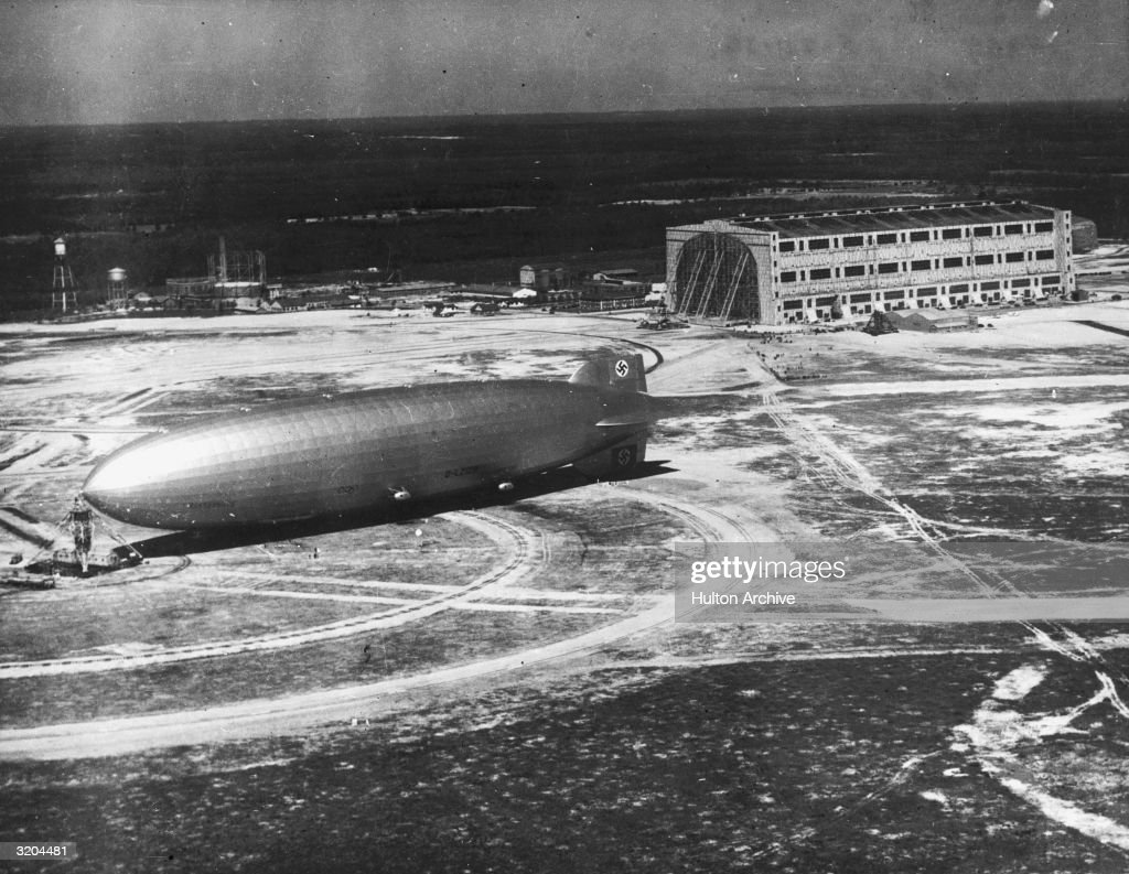 Full-length image of the German-made zeppelin, 'Hindenburg' sitting on an airfield, possibly in Lakehurst, New Jersey. Its tail is decorated with a Nazi swastika.