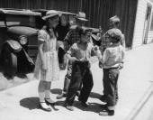 Fulllength image of two boys play fighting while two other boys and a girl watch on a sidewalk in front of some parked cars One of the boys wears...