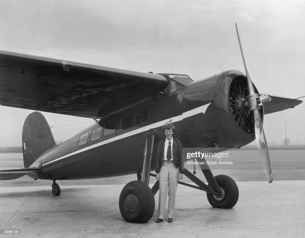 Full-length portrait of American aviator Amelia Earhart (1898 - 1937) posing in front of her airplane on a runway. She was the first woman to fly solo across the Atlantic Ocean.