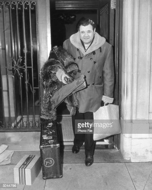Fulllength portrait of baseball legend George Herman 'Babe' Ruth outfielder and slugger for the New York Yankees carrying a fur coat bats in cases...