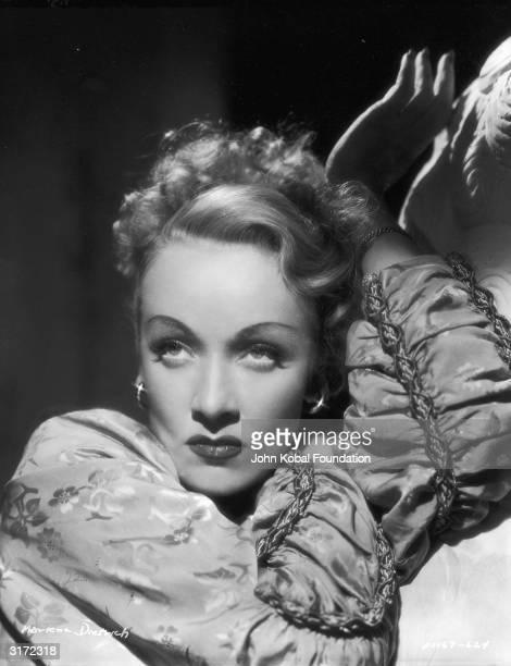 German born American actress Marlene Dietrich posing next to a sculpture