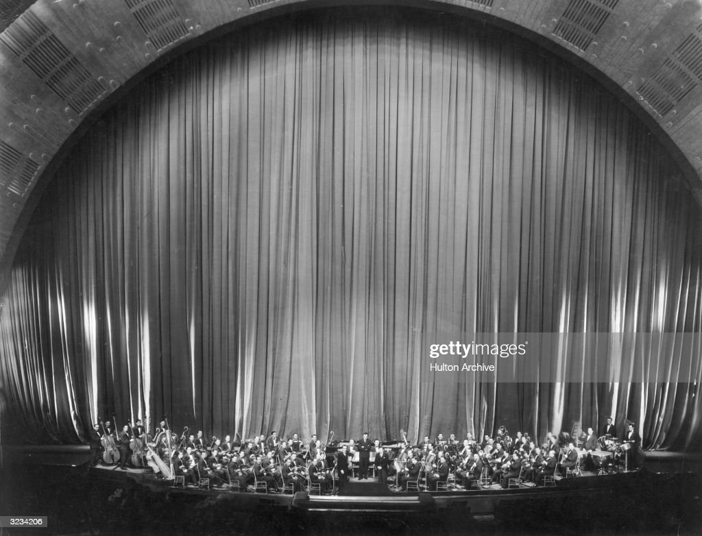 Hungarian-born composer and conductor Erno Rapee (1891 - 1945) poses with the Music Hall Symphony Orchestra at Radio City Music Hall, Rockefeller Center, New York City.