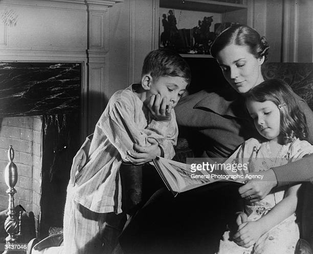 Mother reads a goodnight story by the fireside to her young son and daughter