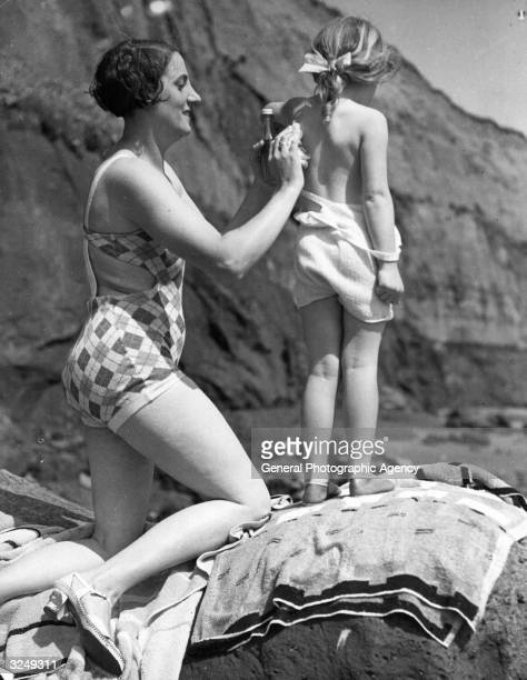 Mum oils her child's back on the beach on the Isle of Wight