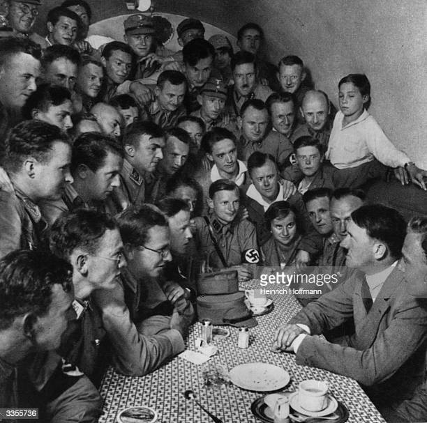 Nazi dictator Adolf Hitler sitting amongst a band of National Socialist youth members of the Reich crowded in to a small room in the 'Braune Haus' or...