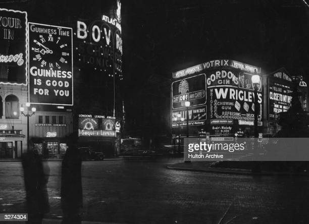 Nightime and two men chat on the street corner with Piccadilly Circus in the background