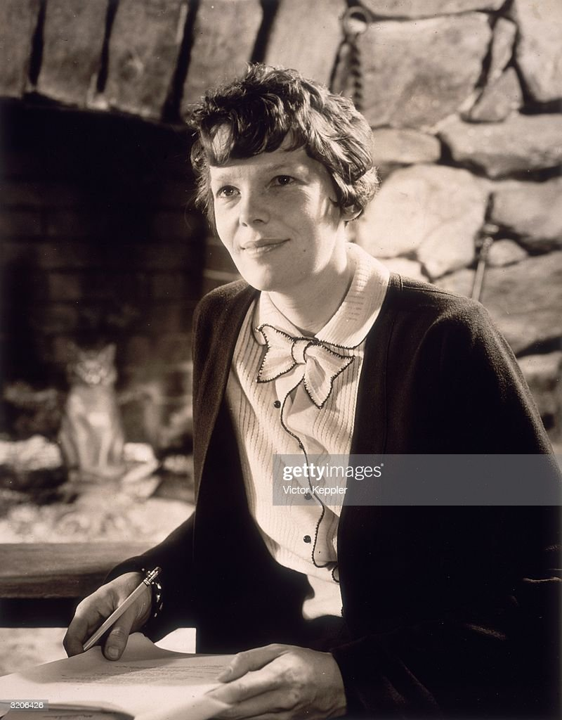 Portrait of American aviator Amelia Earhart (1898 - 1937) sitting inside a stone-walled room with a pencil and a pile of paper. She wears a button-down dress.