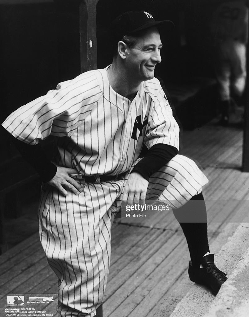 Portrait of American baseball player Lou Gehrig (1903 - 1941), firstbaseman and slugger for the New York Yankees, smiling, while in his uniform, standing on a step of the dugout with one foot and leaning his elbow on his thigh.