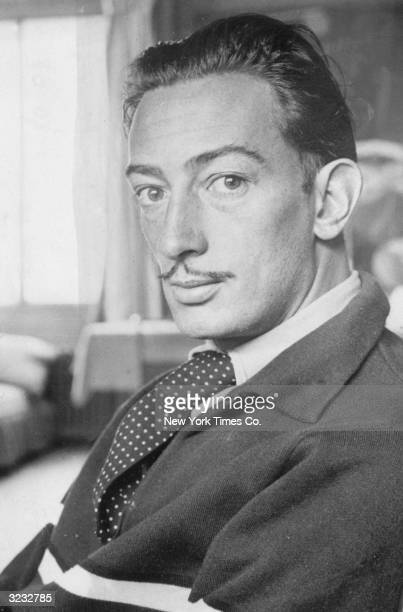 Portrait of Spanish surrealist artist Salvador Dali wearing an ascot tie with a sweater
