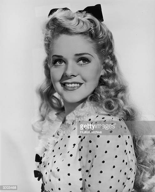 Studio headshot portrait of American singer and actor Alice Faye wearing a polkadot dress smiling while looking over her shoulder