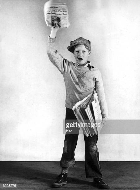 Studio image of a newsboy hawking newspapers 1930s He shouts and displays the headline while holding a bundle of papers under arm He wears a tweed...
