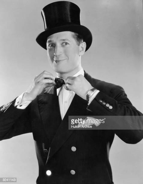 Studio portrait of French cabaret singer and actor Maurice Chevalier wearing a top hat and straightening his bow tie
