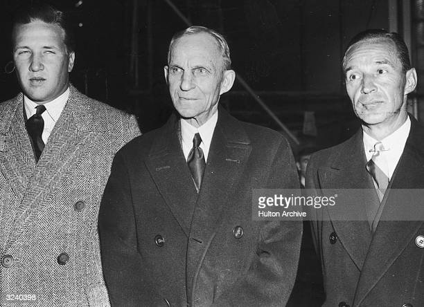 Three generations of Ford automobile executives stand together in winter coats From left to right grandson Henry Ford II his grandfather Henry Ford...