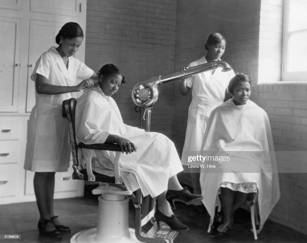 Two female students have their hair styled by two other students at the Bordentown School for Colored youth, New Jersey. The women wear smocks and uniform dresses. One of the stylists uses a large, freestanding hair dryer.