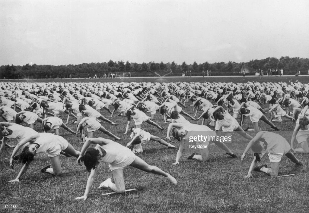 Young Germans of the Hitler Youth Movement wear white vests and shorts as they exercise in a field..