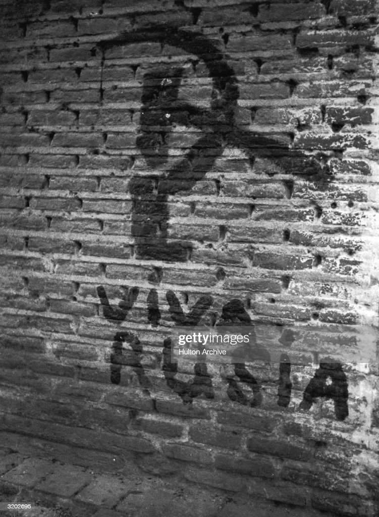 A hammer and sickle are painted on a brick wall somewhere in Spain, Spanish Civil War. The caption below reads, 'Viva Rusia' ('Long Live Russia').