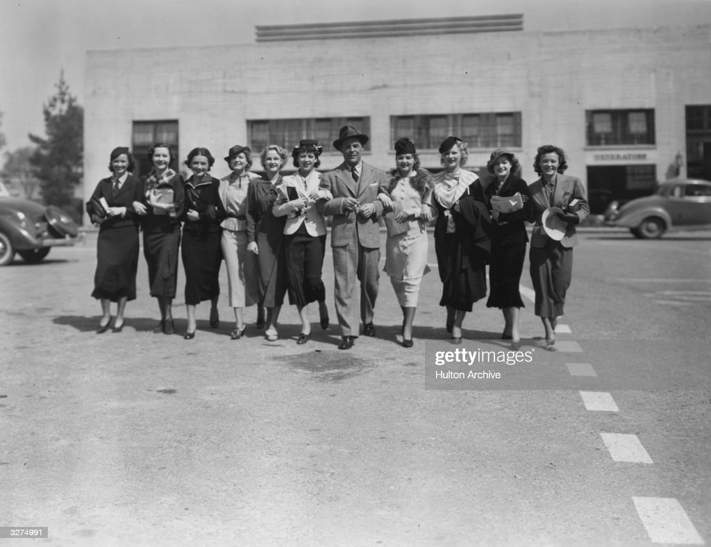 Actor Brian Donlevy with a group of ladies outside the studios of 20th Century Fox where he is starring in Sidney Lanfield's 'Half Angel'