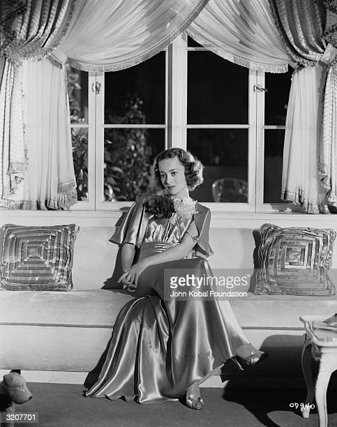 Britishborn actress Olivia de Havilland rests on a window seat in a fulllength satin dress