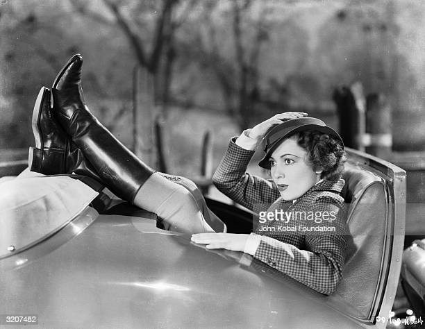 Britishborn actress Olivia de Havilland squeezes into the back seat of a convertible