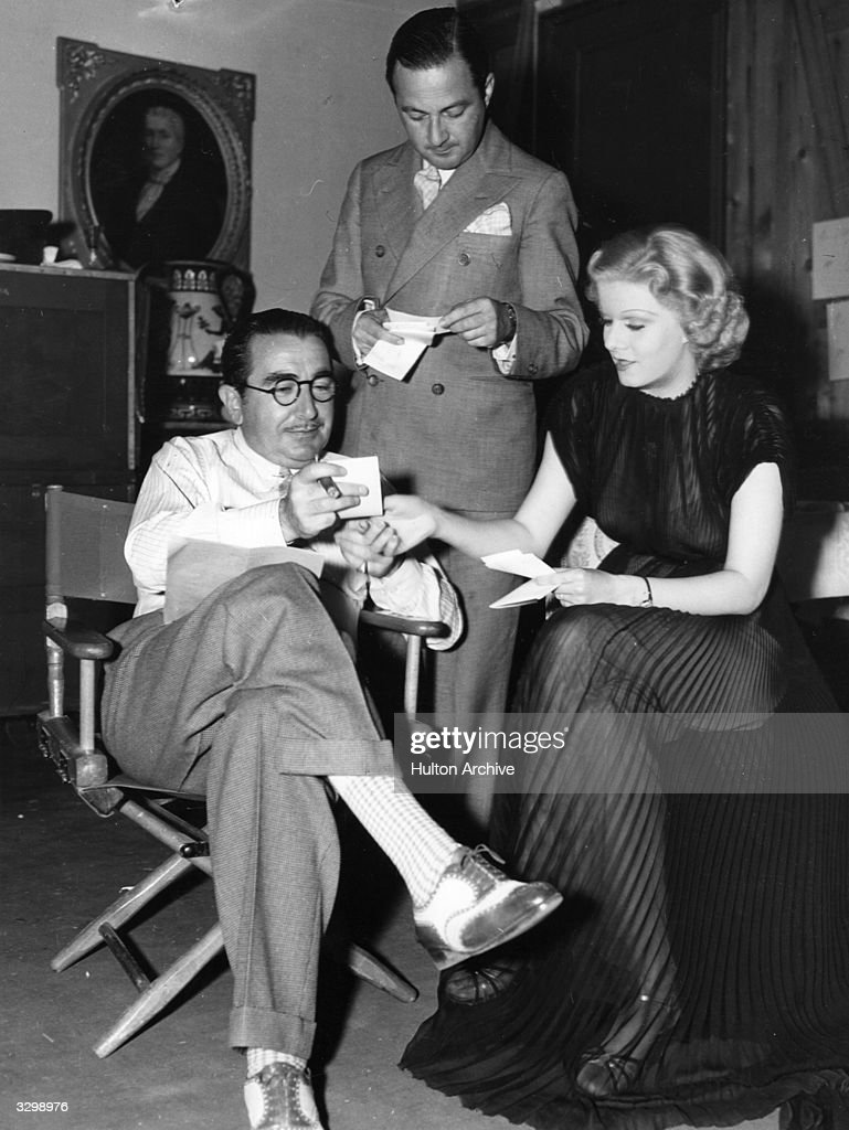 Jean Harlow (1911 - 1937) shows an amusing fan letter to director George Fitzmaurice (1885 - 1940) and Maurice Revnes during the filming of Metro Goldwyn Mayer's 'Suzy'.