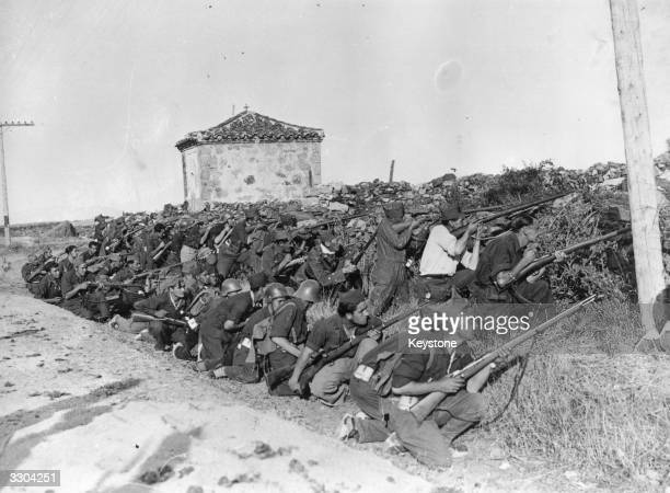 Rebel troops shelter behind a wall near a mountain road on the Sierra de Guadarrama front while they engage government troops during the advance on...