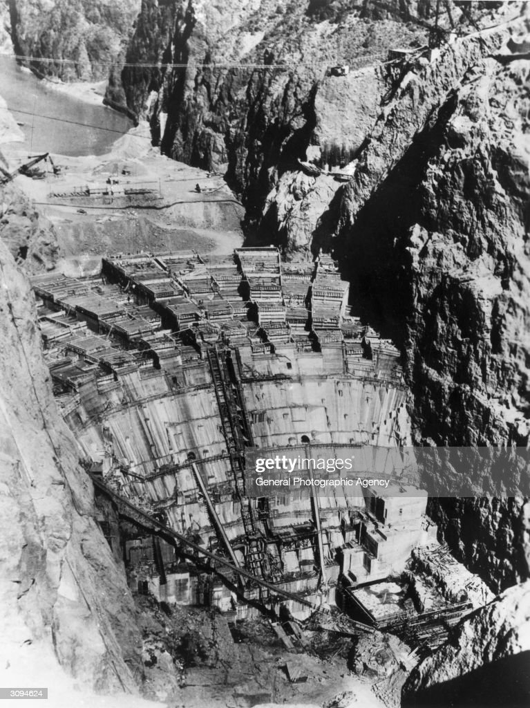The Boulder Dam on the Colorado River under construction. A cable railway runs over it.