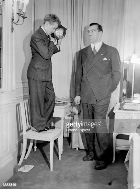 A photographer is forced to stand on a chair to get a good shot of Italian heavyweight boxer Primo Carnera