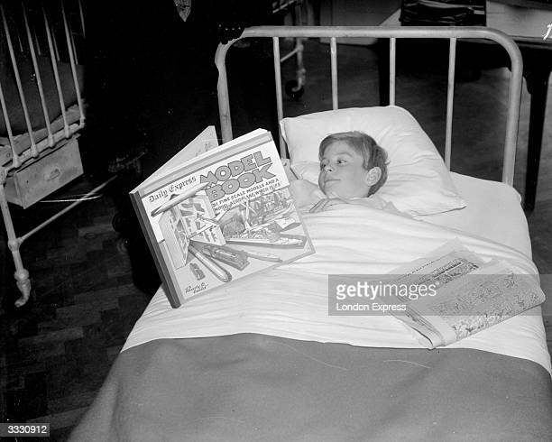 A sick boy in a hospital bed reading the Daily Express Model Book
