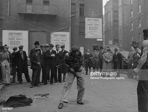 A small crowd in a street in Soho London watch a man trying to extract himself from chains